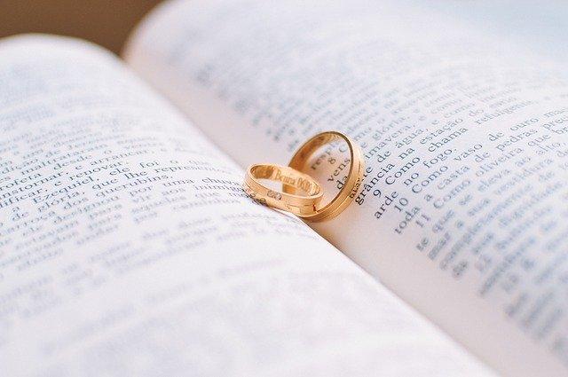 Imagem de Bíblia aberta com duas alianças em ouro amarelo dentro