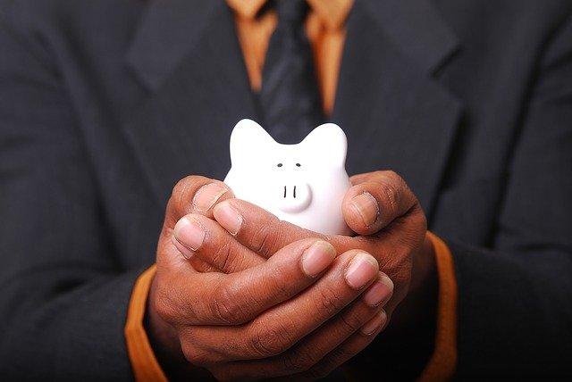 Imagem de homem segurando cofre de porquinho branco