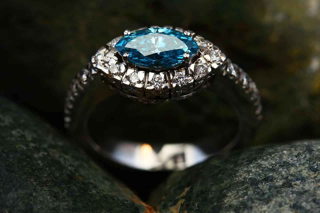 Imagem de anel de noivado com pedra solitária azul e diamantes em volta