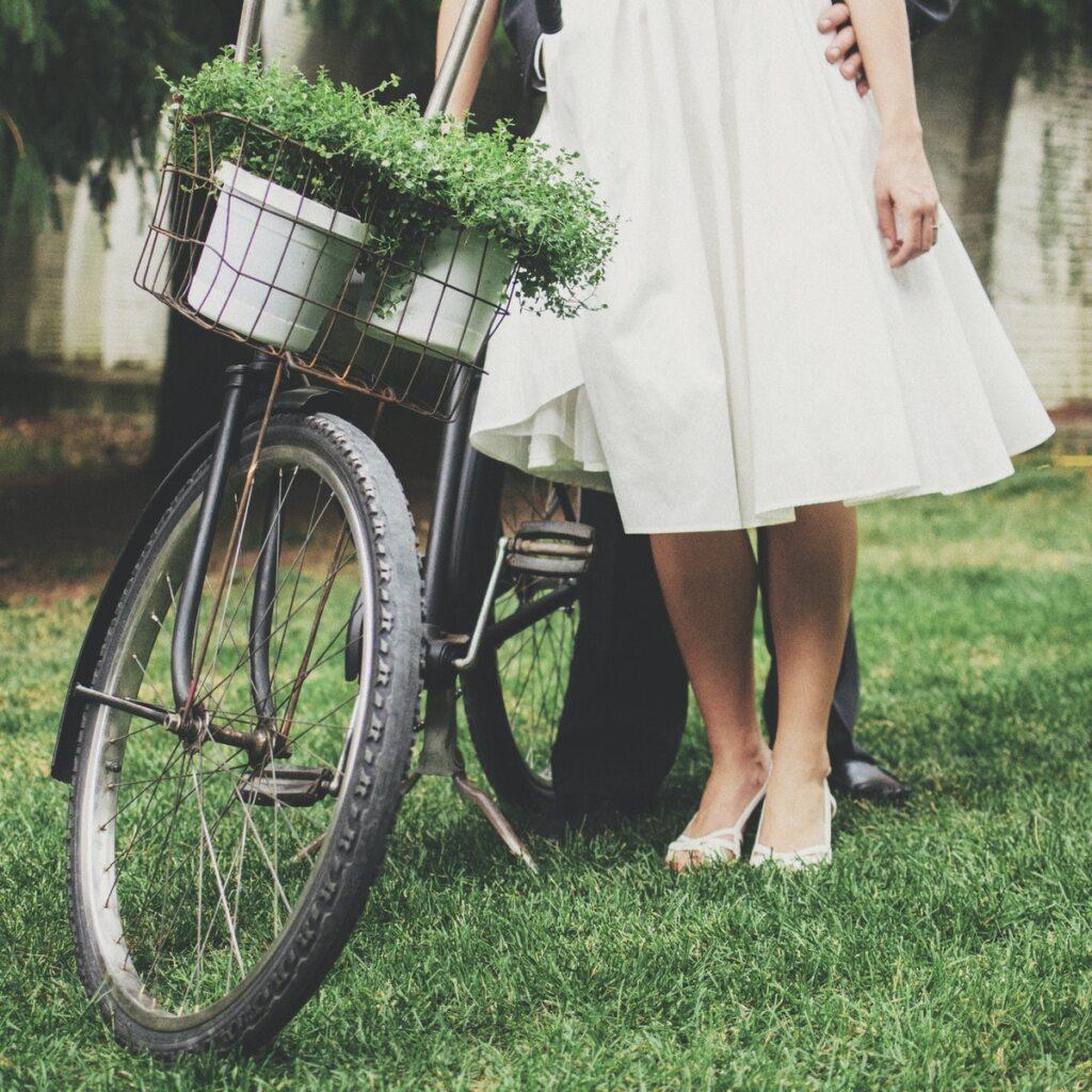 Imagem de casal vestido para casar ao lado de bicicleta