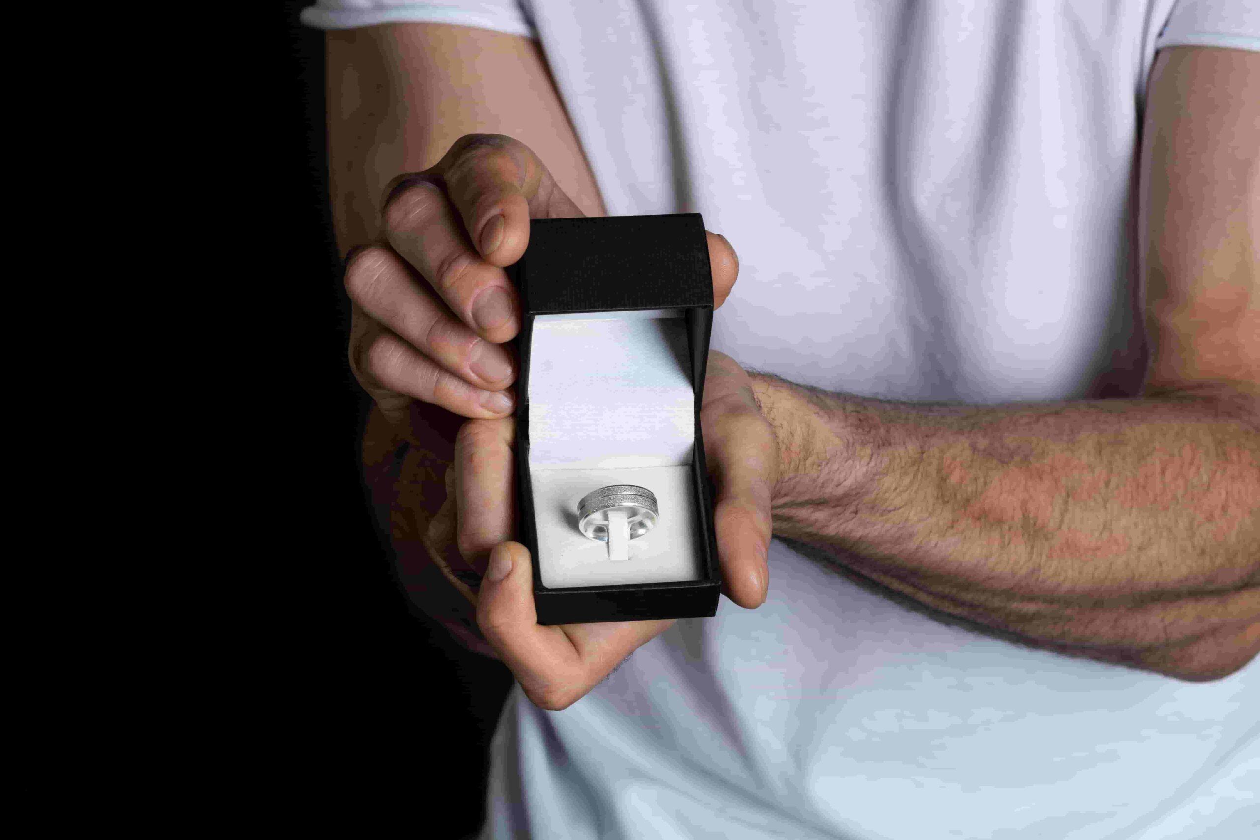 Imagem de homem segurando caixa de anel com aliança dentro