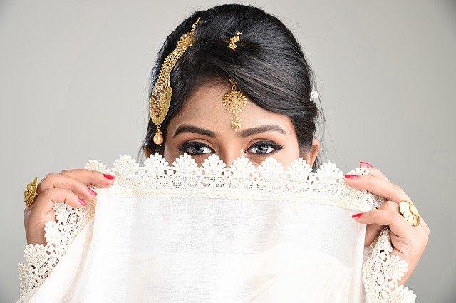 Imagem de mulher indiana com véu sob boca e nariz com joias na cabeça e mãos