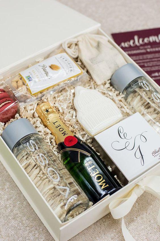 Imagem de welcome box de casamento contendo água, mini champanhe, biscoitos e outros.