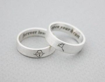 Imagem de alianças prateadas com gravação de cadeado em forma de coração e chave do lado externo