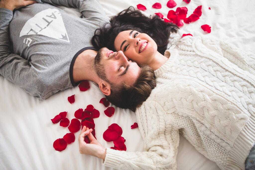 Imagem de casal deitado na cama com pétalas de rosas vermelhas ao redor, com rostos colados um no outro